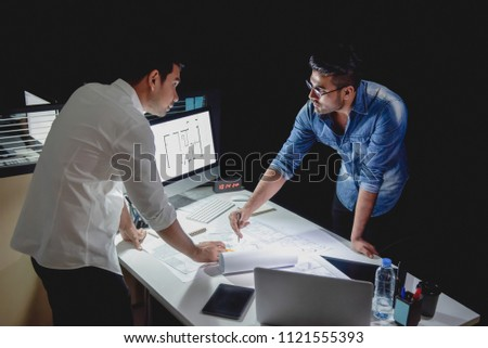 Asian architect team staying late at night in office discussing floor plan design project at meeting table #1121555393