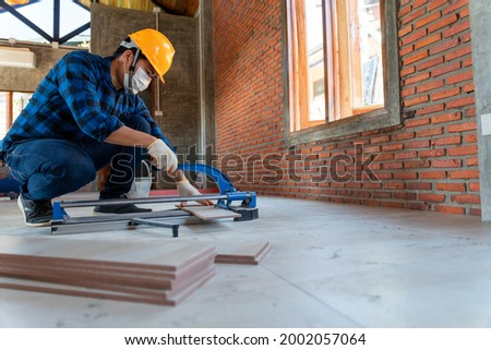 Asian artisan tiler at construction site, worker cuts a large slab of tile during the construction of a house, floor tile cutting equipment Foto stock ©