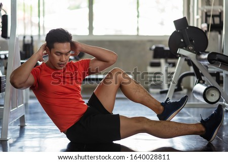 Photo of  Asian Athlete muscle man doing bicycle crunch to build six packs (upper and lower abs and the obliques) in fitness gym. Bodybuilding, sport, and healthy lifestyle concept.