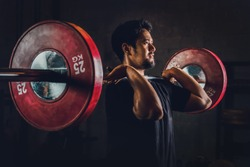 asian athletic strong man having workout and bodybuilding with barbells weightlifting front squat style in gym and fitness center in dark tone, selective focused