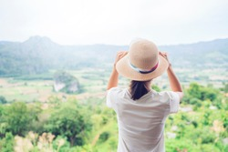 Asian attractive young woman traveler tourist hiking wearing hat back view standing silhouette looking at mountain nature landscape view scenery, hot summer wearing hat feeling peaceful joyful happy