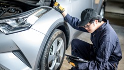 Asian auto mechanic holding digital tablet checking car wheel and tire in auto service garage. Mechanical maintenance engineer working in automotive industry. Automobile servicing and repair concept