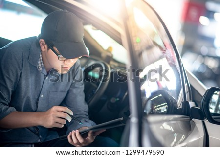 Asian auto mechanic sitting on driver seat checking the car using digital tablet in auto service garage. Mechanical maintenance engineer working in automotive industry. Automobile servicing and repair #1299479590