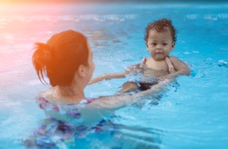 Asian baby boy first time in a swimming pool - Sunset filter effect