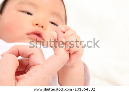 Asian baby boy holding a finger to his mother