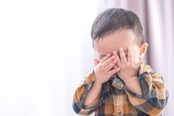Asian baby boy playing hide and seek hiding face with parents,Concepts of learning development of child by playing.