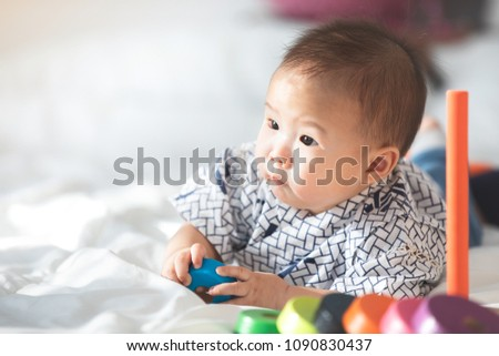 Asian baby boy playing on the bed. #1090830437