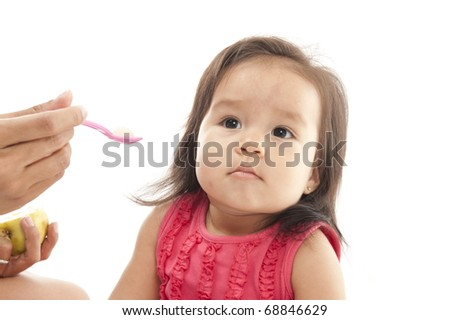 Asian Baby eating fruit with a spoon .