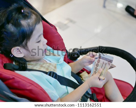 Asian baby girl holding and looking at banknotes - allowing baby to learn and be familiar with money since their early age #1113162551