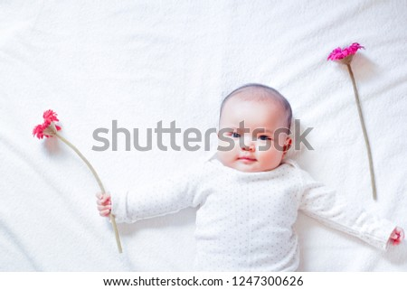 Asian baby girl is holding red and pink flowers on white towel background with sun light shading. Baby girl is plaing with red and pink flower. Baby is happy with her flowers. Zdjęcia stock ©