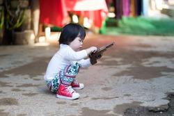 Asian baby girl sitting and playing wood gun.She ware white long shirt tile long leg and red shoes.