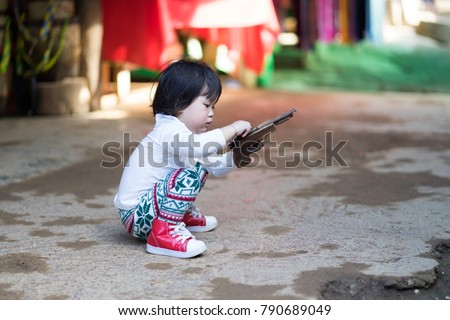 Photo of  Asian baby girl sitting and playing wood gun.She ware white long shirt tile long leg and red shoes.