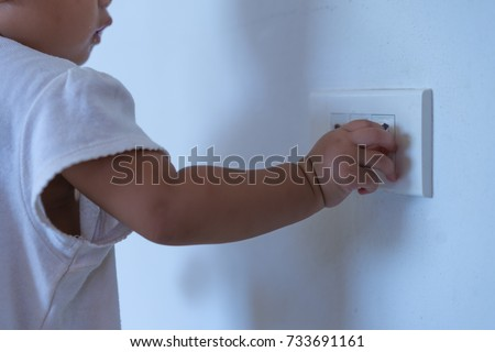 asian baby playing with plug...
