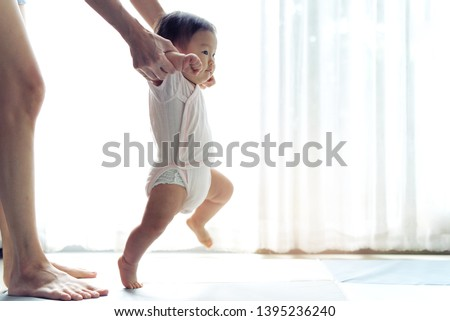 Asian baby taking first steps walk forward on the soft mat. Happy little baby learning to walk with mother help at home. Mother teaching how to walk gently. Baby growth and development concept.