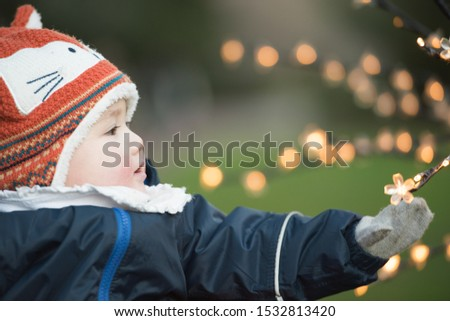 Asian baby wearing winter clothes, mittens and a fox hat reaches out to Christmas light decorations on a tree In Princes Street Gardens, Edinburgh, Scotland, UK