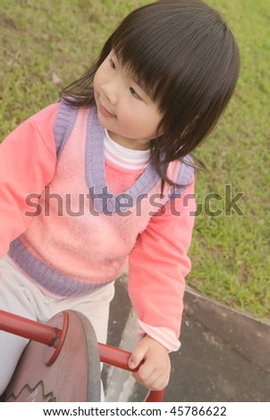 Asian baby with black hair and yellow skin in pink coat play in outdoor of park.