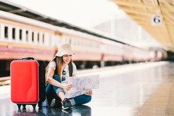 Asian backpack traveler woman using generic local map, siting alone at train station platform with luggage. Summer holiday traveling or young tourist concept