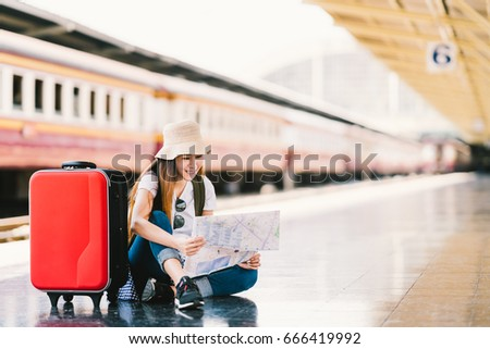 Shutterstock Asian backpack traveler woman using generic local map, siting alone at train station platform with luggage. Summer holiday traveling or young tourist concept