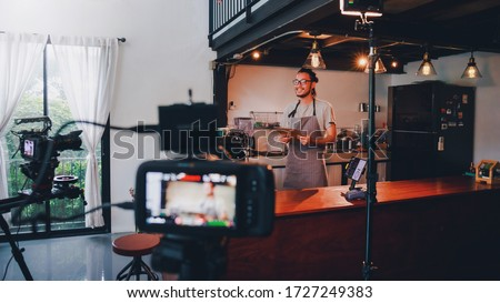 Asian barista man standing in front of the camera and recording vlog video live streaming at bar counter in coffee shop interior background.Sale and promotion online marketing business concept.
