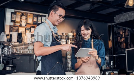 Asian Barista owner training staff using technology on tablet take order from customer in coffee shop ,cafe writing drink order at counter bar,Food and drink business concept,Service mind concept