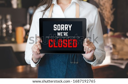 asian barista shop owner holding tablet sign sorry we're closed in front of counter bar. bankrupt business when coronavirus(covid-19) is outbreak in city