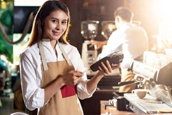 Asian Barista woman make payment with customer credit card using EMV chip technology for coffee purchase at a cafe bar. Cashless preventing from coronavirus covid-19 Spreading and infection.