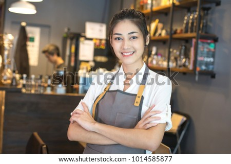 Asian barista woman standing with attractive smiling at front of cafe. Woman success to make sme business.