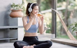 Asian beautiful and sportive woman drinking hot tea and wearing headphone while doing meditation in garden at morning time. Healthy Concept.