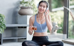 Asian beautiful and sportive woman drinking hot tea, wearing headphone  and listening to music at home in the morning. Healthy Concept.