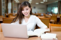 Asian beautiful female student study in library with laptop
