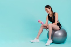 Asian beautiful happy woman holding dumbell and sitting on fit ball after exercise isolated on blue color background.Concept of slim and healthy girl workout.