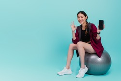 Asian beautiful happy woman holding smartphone and sitting on fit ball after exercise isolated on blue color background wite studio shot.Concept of slim and healthy girl workout.
