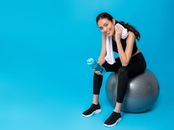 Asian beautiful happy woman holding water bottle and sitting on fit ball after exercise isolated on blue colour background.Concept of slim and healthy girl workout.