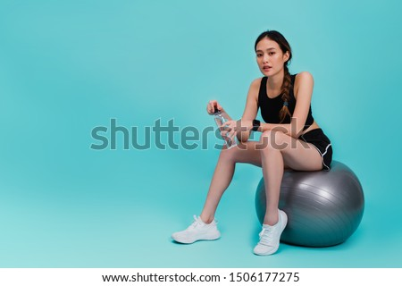 Asian beautiful happy woman holding water bottle and sitting on fit ball after exercise isolated on blue color background.Concept of slim and healthy girl workout.