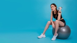 Asian beautiful happy woman wearing smart watch holding water bottle and sitting on fit ball after exercise isolated on blue color background.Concept of slim and healthy girl workout.