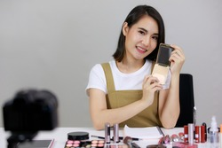 Asian beautiful woman are broadcasting live on smartphones viral video clip by camera and cosmetics makeup in online shopping in the room at home. Concept online shopping Sell
