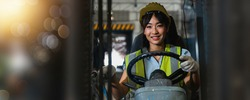 Asian beautiful woman driver drive fork  lift car in industry with smiled, ability of girl and diversity of career wearing helmet in  reflective vest working on vehicle