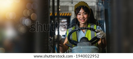 Asian beautiful woman driver drive fork  lift car in industry with smiled, ability of girl and diversity of career wearing helmet in  reflective vest working on vehicle  Foto stock ©