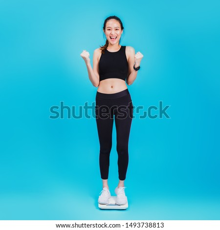 Asian beautiful woman feeling happy and standing on the Weight Scale at blue color background.Concept of weight loss for good health with excercise.