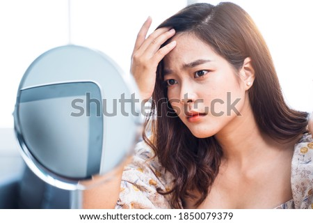 Asian beautiful woman self awareness lack confidence spots pimple zits face problem feeling stress sad worry concern bad unhealthy skin care aging issues looking into mirror, at home in living room  Foto stock ©