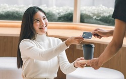 Asian beautiful woman smiling and paying for coffee by credit card. Lifestyle and Finance Concept.