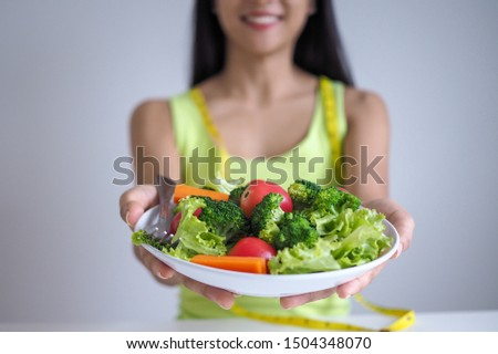 Asian beautiful women are happy to eat salad vegetables. #1504348070