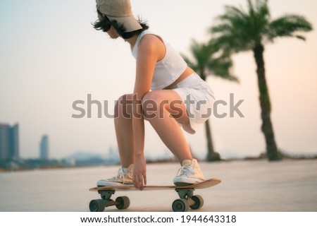 Asian Beautiful women surf skate or skateboard outdoors on beautiful summer day. Happy young women play surf skate at park near the beach on morning time. Sport activity lifestyle concept. Сток-фото ©