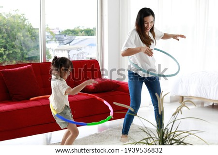 Asian beautiful young long black hair single mom stand smile playing hula hoop together with little cute daughter girl next to red sofa and bed in living bedroom with clear glass windows background.