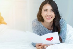 Asian beautiful young woman, long hair, happy smiling reading red heart valentine card on white bed at home. Attractive lovely pretty girl thinking imagine to lover person on morning valentine day.