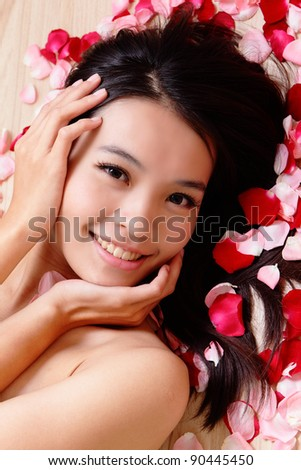 Asian beauty Girl smiling close-up with rose background, Beautiful young woman touching her face looking to the camera