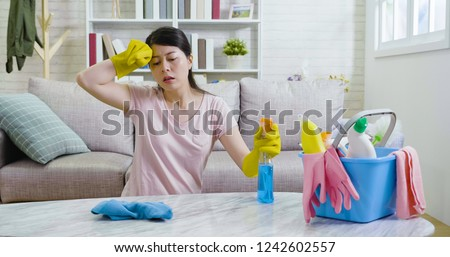 Asian beauty woman hands in gloves wiping sweat off while doing lots of housework at home. young housewife tired sitting on floor cleaning the table holding detergent. cozy living room with sunlights #1242602557