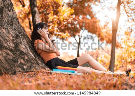 Asian beauty woman listen to the music in park. People lifestyles and Entertainment concept. Relaxation and Vacation concept. Autumn and fall seasonal theme.