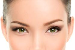 Asian beauty woman with green eyes wearing cat eye smokey eyes eyeliner makeup and mascara. Laser treatment, anti-aging eyelid plastic surgery.