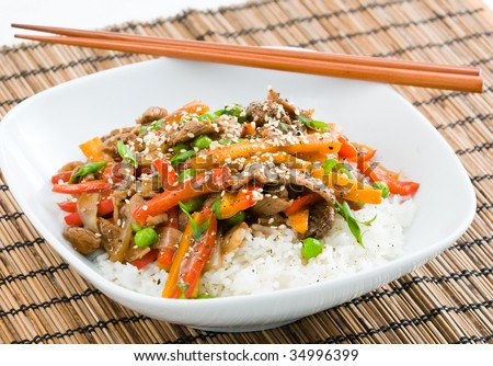 Asian beef stir-fry on rice with peppers carrots onions and peas in black bean sauce